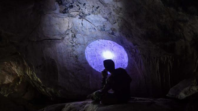 Seorang arkeolog dari Departemen Seni Rupa di Ratchaburi sedang melihat lukisan gua yang baru ditemukan di taman nasional Khao Sam Roi Yot di pesisir provinsi Prachuap Kiri Khan (10/9/2020). (AFP/Lillian Suwanrumpha)