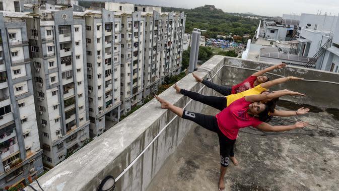Instruktur yoga dari Anahata Yoga Zone melakukan gerakan yoga menjelang Hari Yoga Internasional di teras sebuah bangunan di Hyderabad, India pada 18 Juni 2020. Hari Yoga Internasional atau International Day of Yoga diperingati setiap tahun pada 21 Juni. (Photo by NOAH SEELAM / AFP)