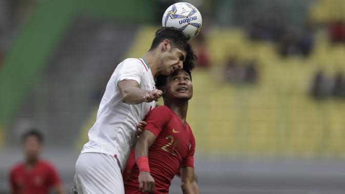 Striker Timnas Indonesia U-19, Bagus Kahfi, berebut bola atas dengan pemain Timnas Iran U-19 pada laga uji coba di Stadion Patriot Chandrabhaga, Bekasi, Sabtu (7/9). Indonesia kalah 2-4 atas Iran. (Bola.com/Yoppy Renato)