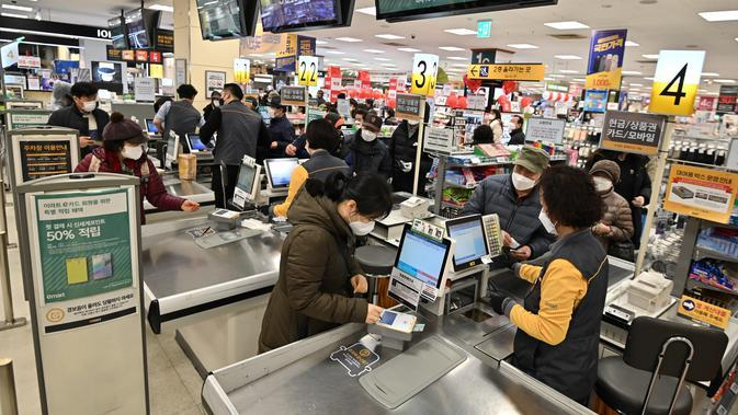Orang-orang membeli masker di toko ritel di kota tenggara Daegu, Selasa (25/2/2020). Korea Selatan menjadi negara pertama di luar Cina daratan dengan infeksi virus COVID-19 terbesar dan membuat presiden Moon Jae-in memberikan status siaga tinggi. (Jung Yeon-je / AFP)