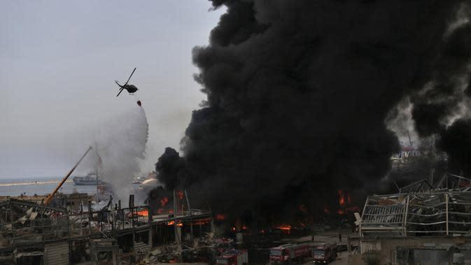 Helikopter tentara menjatuhkan air ke dalam api yang membakar gudang di Pelabuhan Beirut, Lebanon, Kamis (10/9/2020). Kebakaran tersebut menyebabkan kepanikan warga Beirut karena terjadi di lokasi ledakan dahsyat yang menewaskan 200 orang pada bulan lalu. (AP Photo/Hassan Ammar)