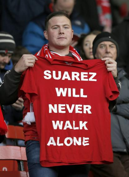 Liverpool fan holds up a football shirt before their English Premier League soccer match against Fulham at Anfield in Liverpool
