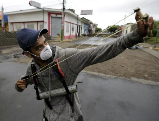 An anti-government demonstrator holding a homemade mortar uses a slingshot during clashes with riot police at a barricade in the town of Masaya, a flashpoint city of anti-government protests demanding President Ortega's ouster