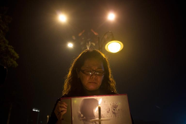 A Malaysian ethnic Chinese woman takes part in a vigil for missing Malaysia Airlines passengers at the Independence Square in Kuala Lumpur on March 10, 2014