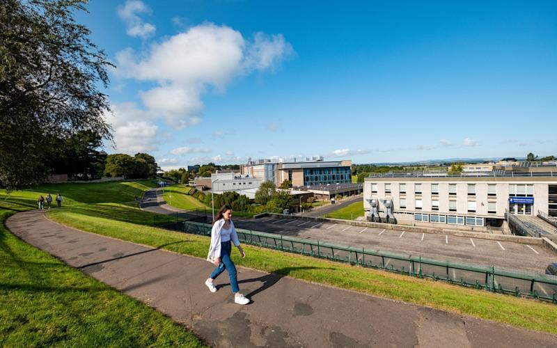 A student at St Andrews leaves the campus at the weekend, when a voluntary lockdown was in force - Stuart Nicol/Stuart Nicol photography