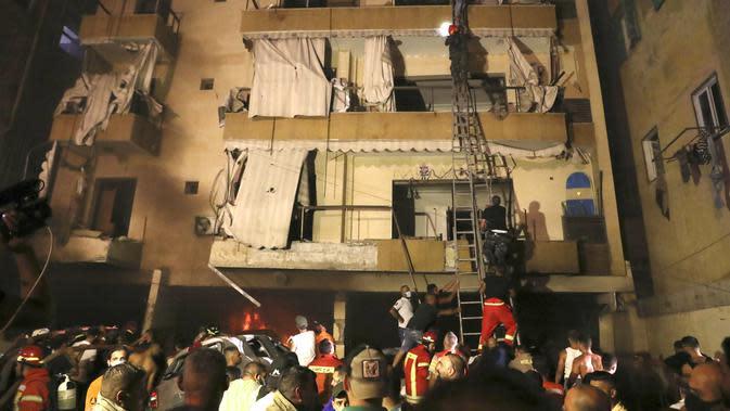 Orang-orang dievakuasi oleh Petugas Pemadam Kebakaran dari apartemen mereka setelah sebuah tangki bensin meledak di lingkungan Tarik al-Jadida, di Beirut, Lebanon (9/10/2020) waktu setempat. (AP Photo/Bilal Hussein)