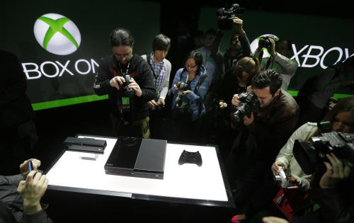 Photographers crowd around Microsoft Corp.'s next-generation Xbox One entertainment and gaming console system after it was officially revealed, Tuesday, May 21, 2013, at an event in Redmond, Wash. It's been eight years since the launch of the Xbox 360. The original Xbox debuted in 2001, and its high-definition successor premiered in 2005. (AP Photo/Ted S. Warren)