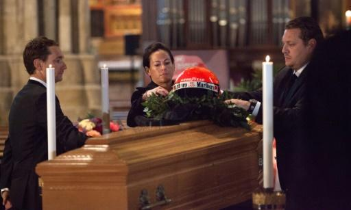 Birgit Lauda (C), the widow of late Austrian former Formula One pilot Niki Lauda, and his son Lukas (R) place Niki Lauda's racer helmet on his coffin