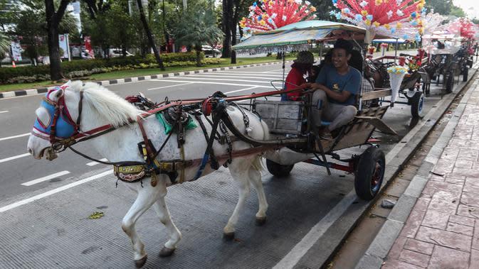 Warga menaiki delman di kawasan IRTI Monas, Jakarta, Jumat (21/8/2020). Jasa sewa delman untuk warga berkeliling kawasan Monas tersebut bertarif Rp50 ribu hingga Rp100 ribu. (Liputan6.com/Johan Tallo)