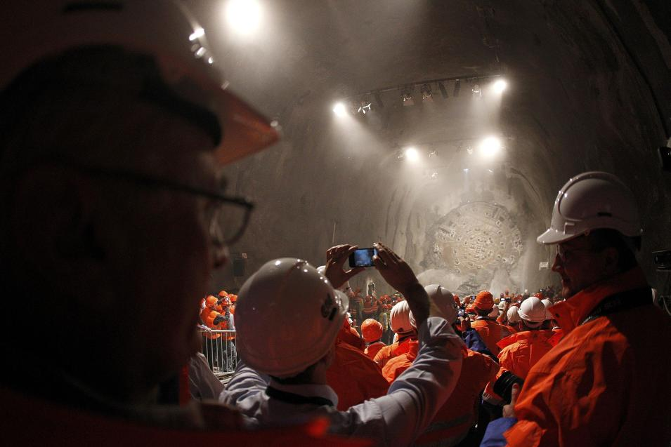 Miners watch as the drill machine 'Sissi' breaks through the rock at the final section Faido-Sedrun, at the construction site of the NEAT Gotthard Base Tunnel Oct. 15, 2010. With a length of 57 km (35 miles) crossing the Alps, the world's longest train tunnel should become operational at the end of 2017.   ((AP Photo/Christian Hartmann,Pool)