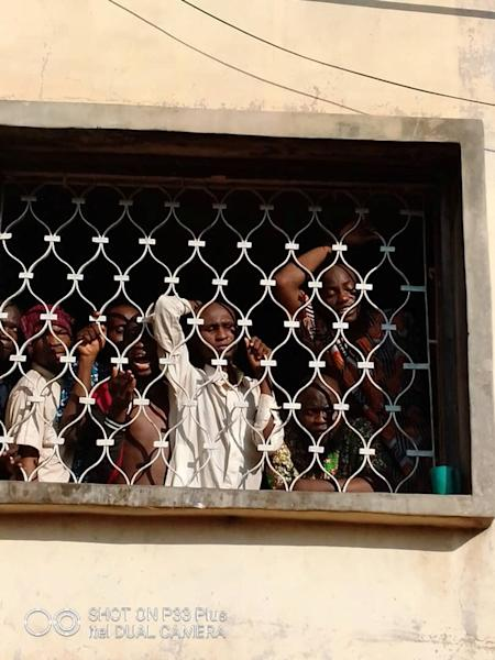 People look out from a window before being freed by police from an Islamic rehabilitation centre in Ibadan