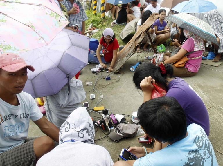 Residents share a power outlet to charge their mobile phones after super typhoon Haiyan hit Tacloban