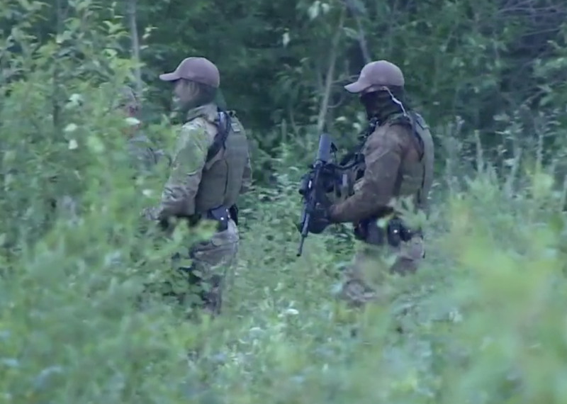 Photo shows two armed RCMP officers in searching bushland for missing teen fugitives Kam McLeod and Bryer Schmegelsky.