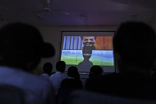 In this Monday, March 25, 2013, photo, Pakistani orphans watch an early screening of the first episode of the animates Burka Avenger series, at an orphanage on the outskirts of Islamabad, Pakistan. Wonder Woman and Supergirl now have a Pakistani counterpart in the pantheon of female superheroes _ one who shows a lot less skin. Meet Burka Avenger: a mild-mannered teacher with secret martial arts skills who uses a flowing black burka to hide her identity as she fights local thugs seeking to shut down the girls' school where she works. Sadly, it's a battle Pakistanis are all too familiar with in the real world.(AP Photo/Muhammed Muheisen)