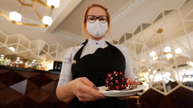 Seorang pramusaji mengambil makanan penutup berbentuk virus corona di sebuah kedai kopi di Praha, Republik Ceko, 5 Oktober 2020. Republik Ceko kembali berlakukan keadaan darurat setelah menghadapi tingkat infeksi Covid-19 yang tinggi. (AP Photo/Petr David Josek)