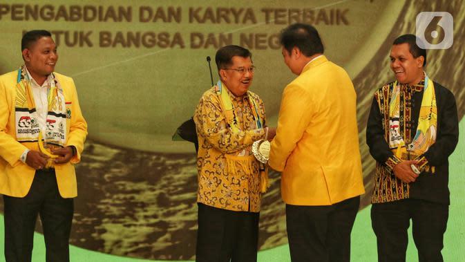 Ketua Umum Partai Golkar Airlangga Hartarto (kedua kanan) memberikan penghargaan kepada Wakil Presiden Indonesia ke-10 dan ke-12 Jusuf Kalla dalam peringatan HUT ke-55 Partai Golkar di Jakarta, Rabu (6/11/2019). (Liputan6.com/JohanTallo)