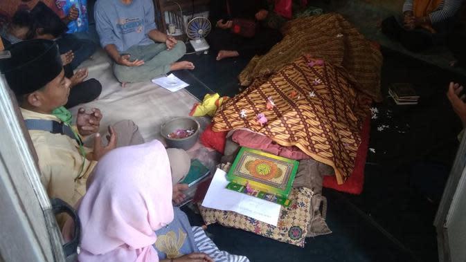 Keluarga TG membaca doa di depan jasad TG, korban tenggelam di Sungai Musi Palembang Sumsel (Liputan6.com / Nefri Inge)