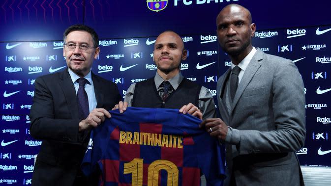 Penyerang baru Barcelona, Martin Braithwaite berpose dengan presiden klub Spanyol Josep Maria Bartomeu dan sekretaris teknis Barcelona Eric Abidal selama presentasi dirinya di Barcelona, Spanyol (20/2/2020). (AFP/Josep Lago)