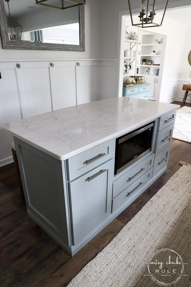 """<p>This DIY built-in kitchen island was made from big box store cabinets and has undergone several makeovers since it was first constructed. The latest features a lovely green-blue paint upgrade, new bar pulls, and of-the-moment shaker door panels. </p><p><strong>Get the tutorial at <a href=""""https://www.artsychicksrule.com/diy-kitchen-island-makeover/"""" target=""""_blank"""">Artsy Chicks Rule</a>. </strong></p><p><a class=""""body-btn-link"""" href=""""https://www.amazon.com/Prestige-Paints-Interior-Semi-Gloss-Comparable/dp/B01N9IR0MT/?tag=syn-yahoo-20&ascsubtag=%5Bartid%7C10050.g.31102255%5Bsrc%7Cyahoo-us"""" target=""""_blank"""">SHOP BLUE-GREEN PAINT</a></p>"""