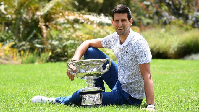 Petenis Serbia, Novak Djokovic berpose dengan piala juara tunggal putra Australia Terbuka 2020 saat sesi pemotretan di Royal Botanic Gardens Victoria, Melbourne, Australia, Senin (3/2/2020). Djokovic sudah mengoleksi sebanyak 17 gelar grand slam dengan kemenangan kali ini. (Photo by William WEST / A