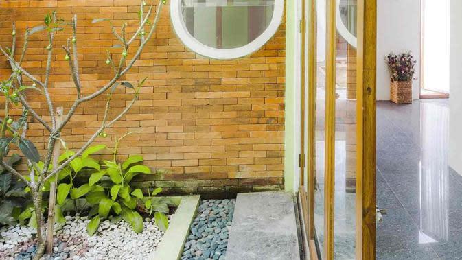Desain jendela bundar dan dinding bata ekspos rumah mungil karya Ruangan Asa. (dok. Ruangan Asa/Arsitag)