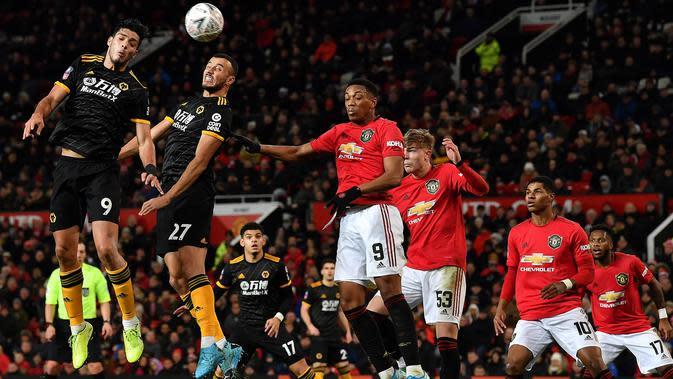 Pemain Wolverhampton Wanderers Raul Jimenez (kiri) menyundul bola ke gawang Manchester United pada putaran ketiga Piala FA di Old Trafford, Manchester, Inggris, Rabu (15/1/2020). Manchester United menang 1-0. (PAUL ELLIS/AFP)