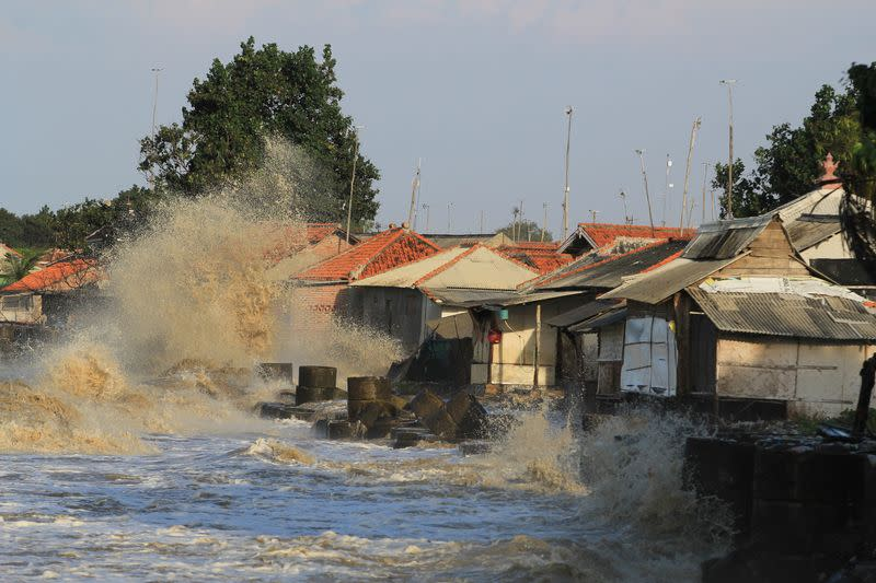Houses are hit by a wave on a beach during tide in Indramayu
