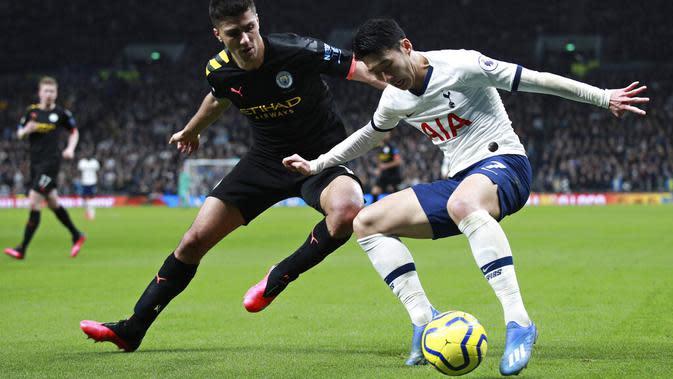 Penyerang Tottenham Hotspur, Son Heung-min, berebut bola dengan pemain Manchester City, Rodrigo, pada laga Premier League di Stadion Tottenham Hotspur, Minggu (2/2/2020). Tottenham menang 2-0 atas Manchester City. (AP/Ian Walton)