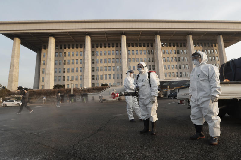"""Workers wearing protective suits spray disinfectant as a precaution against the coronavirus at the National Assembly in Seoul, South Korea, Monday, Feb. 24, 2020. South Korea reported another large jump in new virus cases Monday a day after the the president called for """"unprecedented, powerful"""" steps to combat the outbreak that is increasingly confounding attempts to stop the spread. (AP Photo/Ahn Young-joon)"""