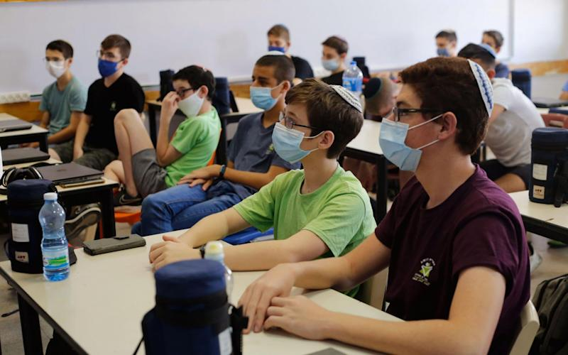 Students wearing masks are seen in a classroom in central Israeli city of Modiin
