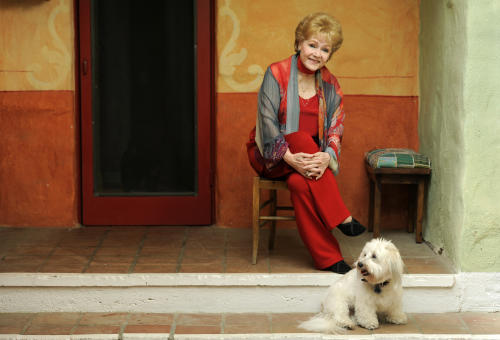 "In this Tuesday, May 21, 2013 photo, Debbie Reynolds, a cast member in the film ""Behind the Candelabra,"" poses for a portrait with her dog, Dwight, in Beverly Hills, Calif. Reynolds plays Frances, the mother of the pianist and vocalist, Liberace. HBO debuts ""Behind the Candelabra"" in the US, Sunday, May 26, 2013. (Photo by Chris Pizzello/Invision/AP"