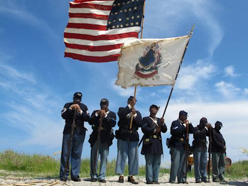 "Black re-enactors in a color guard pray on Morris Island near Charleston, S.C., on Thursday, July 18, 2013 during a observance of the 150th anniversary of the charge of the black 54th Massachusetts Volunteer Infantry in a fight commemorated in the film ""Glory."" (AP Photo/Bruce Smith)"