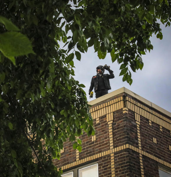 Obediah, a member of a neighborhood watch that started after the death of George Floyd in police custody sparked unrest, looks out from the roof of his home with binoculars, Tuesday June 2, 2020, in Minneapolis, Minn. A week of civil unrest has led some Minneapolis residents near the epicenter of the violence to take steps to protect their homes and neighborhoods. (AP Photo/Bebeto Matthews)