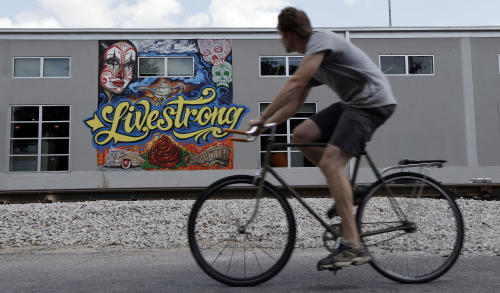 A cyclist passes a mural on the Lance Armstrong foundation building, Friday, Aug. 24, 2012, in Austin, Texas. The U.S. Anti-Doping Agency stripped Armstrong of his seven Tour de France titles Friday, erasing one of the most incredible achievements in sports after deciding he had used performance-enhancing drugs to do it. (AP Photo/Eric Gay)