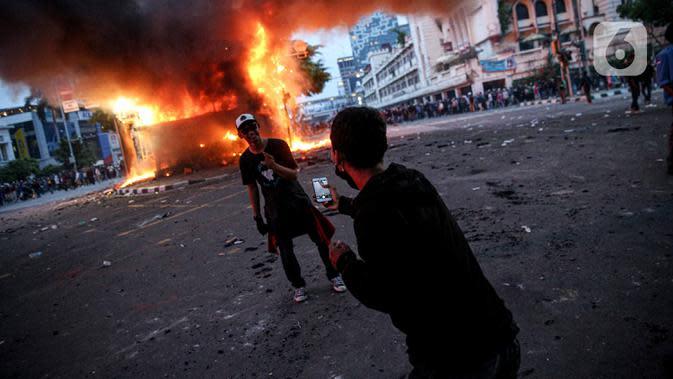 Seorang pria berfoto di depan pos polisi yang terbakar di kawasan Harmoni, Jakarta, Kamis (8/10/2020). Bentrokan pecah saat massa yang hendak menuju Istana Negara untuk menggelar unjuk rasa menolak UU Cipta Kerja diadang oleh aparat kepolisian. (Liputan6.com/Faizal Fanani)