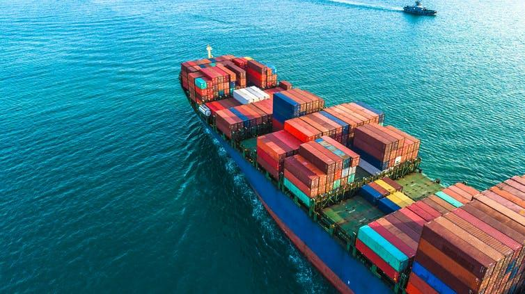 Aerial view of ship loaded with shipping containers in ocean