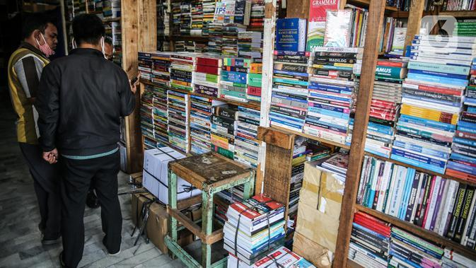 Pengunjung melihat buku di salah satu kios, kawasan Kwitang Jakarta, Jumat (26/6/2020). Sejumlah pedagang mengaku penjualan buku mengalami penurunan hingga 50 persen karena imbauan Pemerintah untuk tinggal dirumah dan libur sekolah selama pandemi COVID-19. (Liputan6.com/Faizal Fanani)