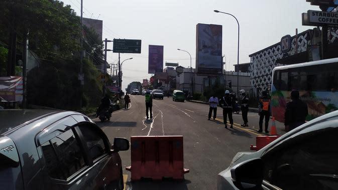 Petugas gabungan menutup jalan menuju kawasan Puncak Bogor, Sabtu (12/9/2020). Polisi menerapkan rekayasa lalu lintas satu arah untuk mengurai kepadatan di kawasan Puncak. (Liputan6.com/Achmad Sudarno)