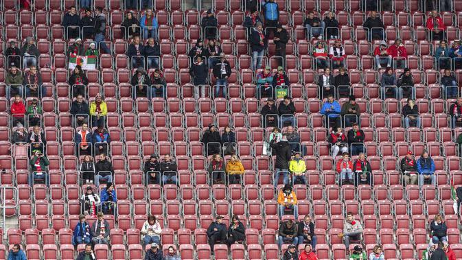 Suporter saat menyaksikan pertandingan antara FC Augsburg melawan Borussia Dortmund pada laga Bundesliga, Sabtu (26/9/2020). Sejumlah liga di Eropa telah mengijinkan fans menonton langsung pertandingan di stadion. (Matthias Balk/dpa via AP)