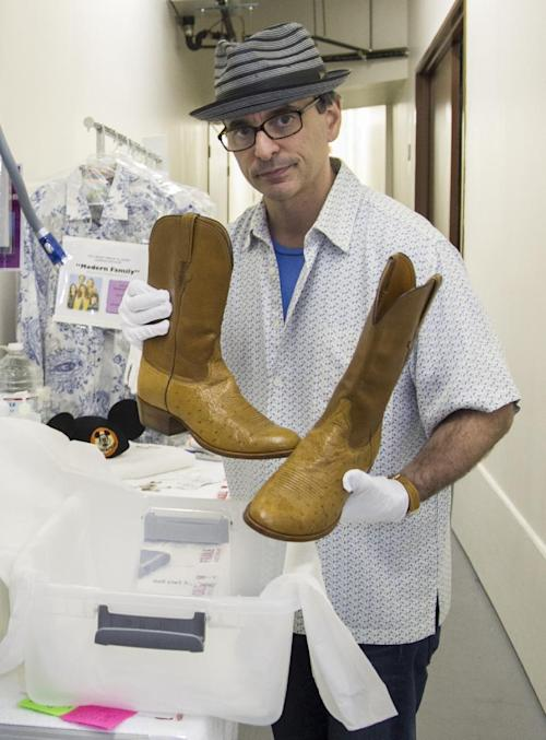 """In this Friday, Nov. 30, 2012 photo, James Comisar shows boots worn by actor Larry Hagman as oil tycoon J. R. Ewing in the TV show """"Dallas."""" The item is part of his television memorabilia collection in a temperature- and humidity-controlled warehouse in Los Angeles. (AP Photo/Damian Dovarganes)"""