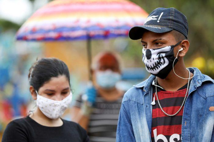 A young man and woman wear face masks at a funeral