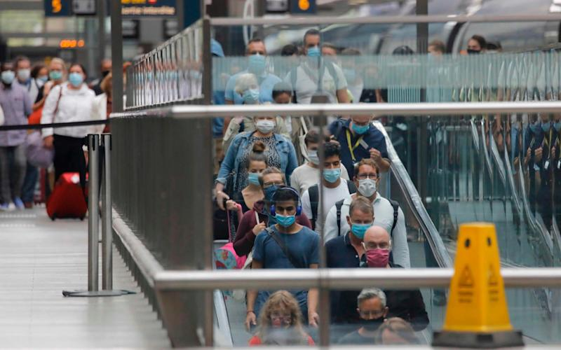 Passengers wearing facemasks as a precaution against the spread of the novel coronavirus walk along the platform to an escalator after arriving on a Eurostar train from Paris at St Pancras International station in London - TOLGA AKMEN/AFP