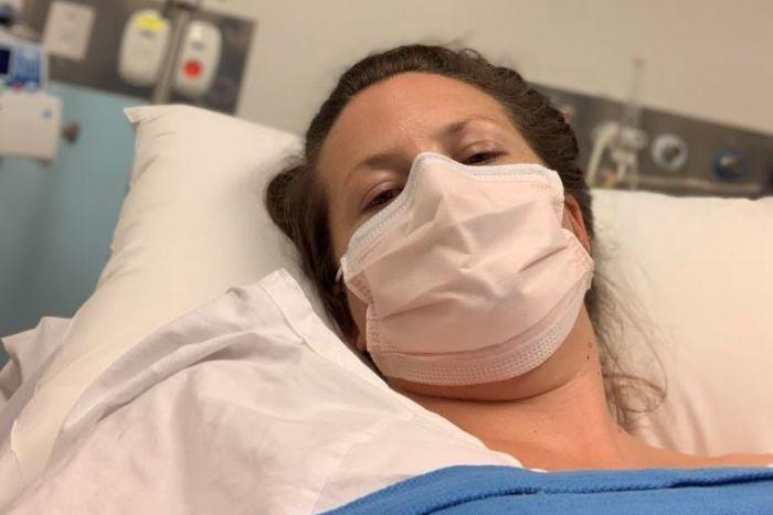 Byron Bay woman Mirabai Nicholson-McKellar lies in a hospital bed wearing a face mase as she is trated for COVID-19.