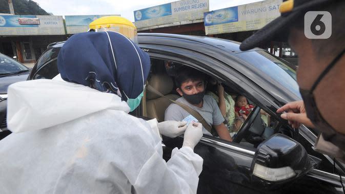 Petugas memeriksa surat keterangan lolos uji rapid test pada warga yang akan melakukan perjalanan di Pos Pam Puncak Pass, Jawa Barat, Minggu (17/5/2020). Ratusan kendaraan dipulangkan ke daerah asalnya dari wilayah Bogor Depok dan Jakarta karena melanggar PSBB parsial. (merdeka.com/Arie Basuki)