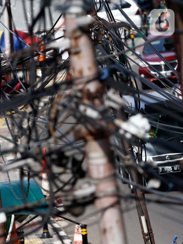 Kendaraan melintas di bawah kabel listrik dan kabel optik yang terlihat semrawut di kawasan Taman Puring, Jakarta, Jumat (3/7/2020). Tidak ada aturan yang baku membuat satu tiang listrik bisa digunakan berbagai kabel baik itu listrik ataupun optik dari berbagai provider. (Liputan6.com/Johan Tallo)