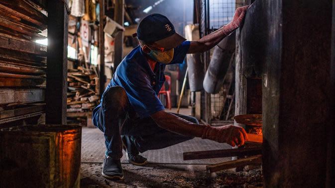 Pekerja memeriksa kayu bakar sebelum memanggang biji kopi di Pabrik Kopi Antong, Taiping, Perak, Malaysia, 29 September 2020. Pabrik Kopi Antong menggunakan mesin antik dan metode pemanggangan tradisional untuk menghasilkan bubuk sarat kafein yang terkenal selama 87 tahun. (Mohd RASFAN/AFP)