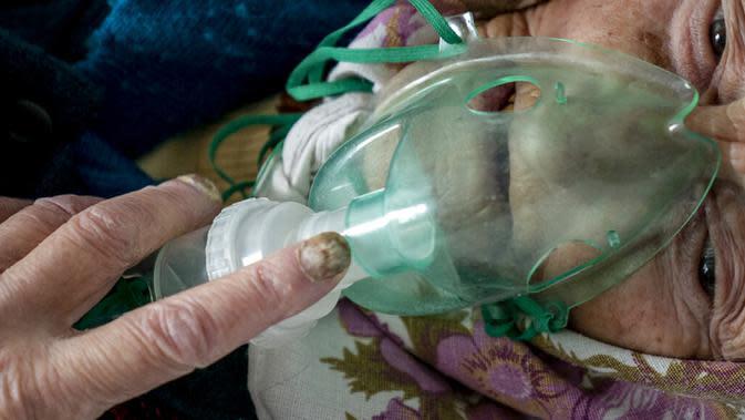 Seorang wanita lanjut usia yang menderita COVID-19 bernapas dengan oksigen di sebuah rumah sakit di Pochaiv, Ukraina, 1 Mei 2020. Total kasus COVID-19 di Ukraina sebanyak 201.305 kasus, 3.996 kematian, dan 88.453 orang telah pulih. (AP Pohto/Evgeniy Maloletka)