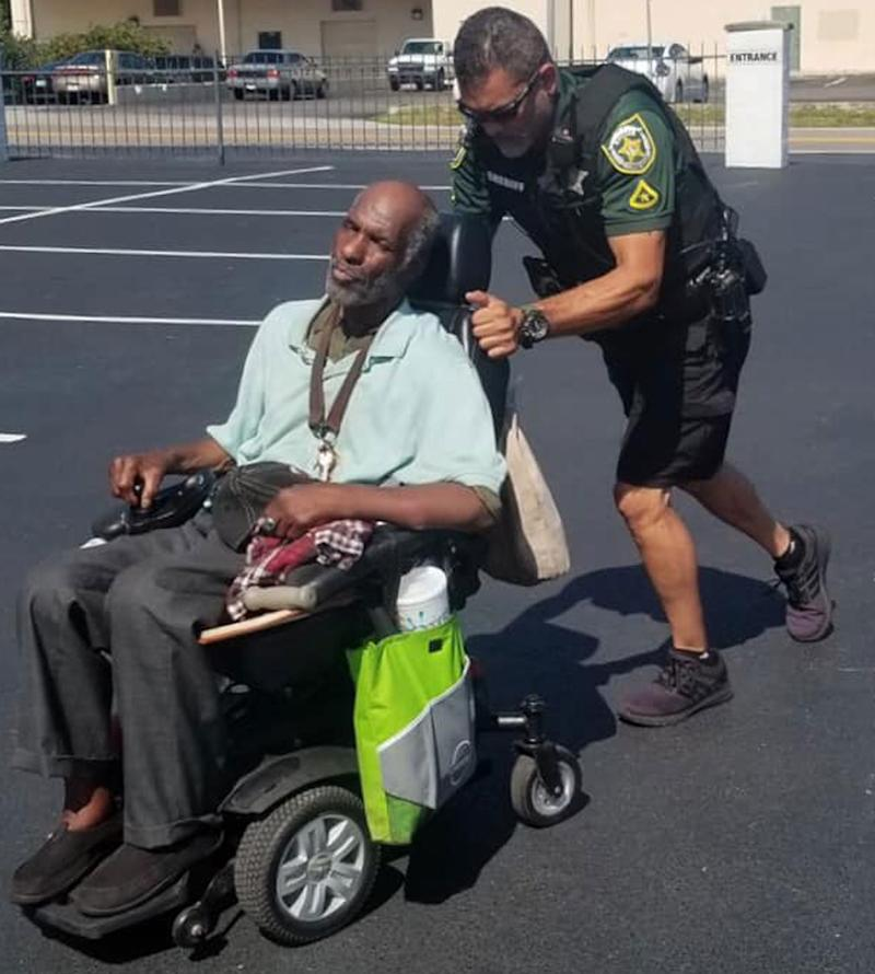 Deputy Danny Garciapagan seen pushing a man in a broken down electric wheelchair. The deputy pushed the chair with the man in it uphill and into a church for shelter as it was 32C outside.
