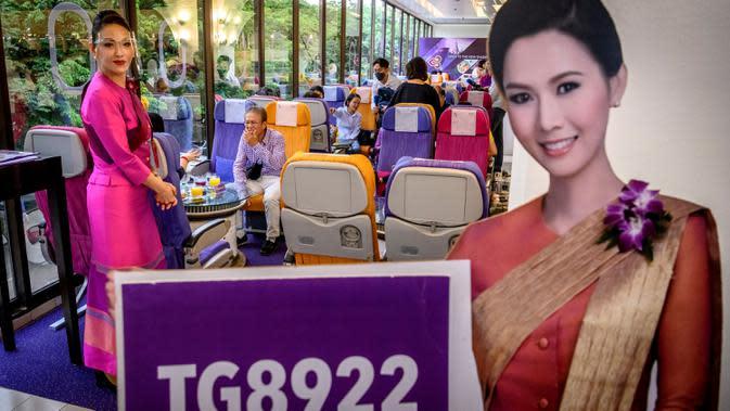 Seorang pramugari mengenakan pelindung wajah di restoran pop-up bertema kabin pesawat di kantor pusat Thai Airways di Bangkok, 10 September 2020. Rencananya, kantor Thai Airways lainnya akan diubah menjadi restoran bertema kabin pesawat untuk memberi pengalaman bersantap serupa. (Mladen ANTONOV/AFP)