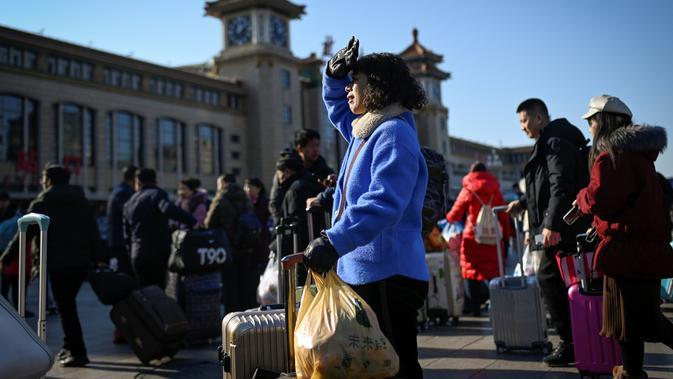 Seorang wanita dengan koper dan bawaannya menunggu untuk masuk ke stasiun kereta api Beijing, Jumat (10/1/2020). Puluhan ribu warga China telah meninggalkan kota-kota besar China menuju kampung halaman, guna merayakan Tahun Baru Imlek yang akan jatuh pada 25 Januari mendatang. (WANG ZHAO/AFP)